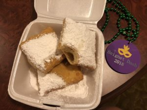 Three beignets and a medal from the Port Orleans French Quarter Beignet Dash