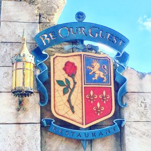 Medieval sign in front of the Be Our Guest Restaurant in Walt Disney World, Blue and red and gold coloured sign, Medieval Sconce, Shield Shape sign with a red rose, a lion and florals to signify the Beauty and the Beast movie