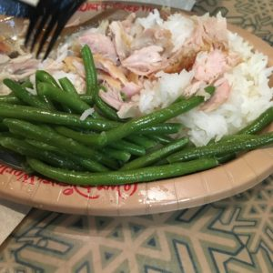 Allergy-friendly Quick Service Meal, eating Green beans with rice and shredded chicken and a black fork.